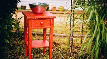 Un comodino rosso con una vaschetta tonda di ottone a simboleggiare il qui e ora.